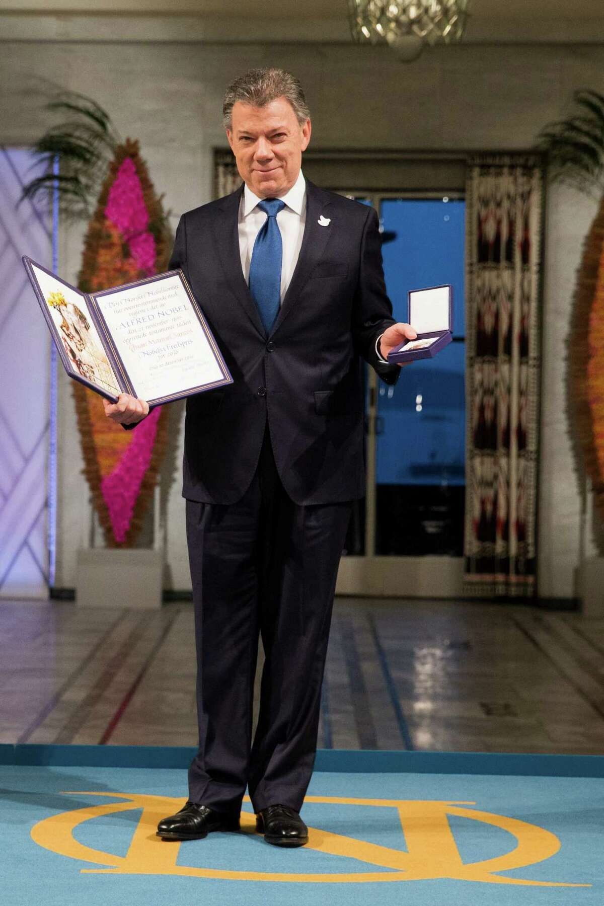 Nobel Peace Prize Laureate Colombian President Juan Manuel Santos poses with the medal and diploma following the Nobel awarding ceremony at the City Hall in Oslo, Saturday Dec. 10, 2016. Colombian President Juan Manuel Santos is awarded this year's Nobel Peace Prize for his efforts to bring Colombia's more than 50-year-long civil war to an end. (Haakon Mosvold Larsen/ NTB scanpix via AP)