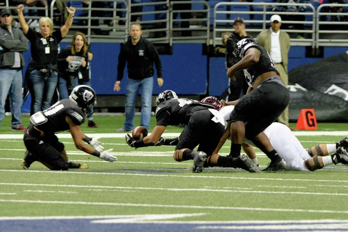 Cibolo Steele players jump on a fumble made by James Klingler (12) of Cinco Ranch in the first half of the Conference 6A Division II State Semi-Final playoff game between the Cinco Ranch Cougars and the Cibolo Steele Knights on Saturday December 10, 2016 at the Alamodome, San Antonio, TX.