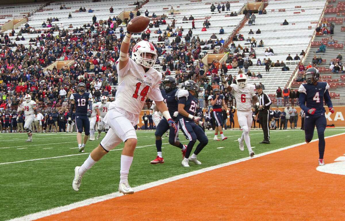 The Woodlands' Grant Murphy holds up the ball as he scores on an 8-yard pass from Eric Schmid during the Class 6A Division I state semifinal game in Austin.