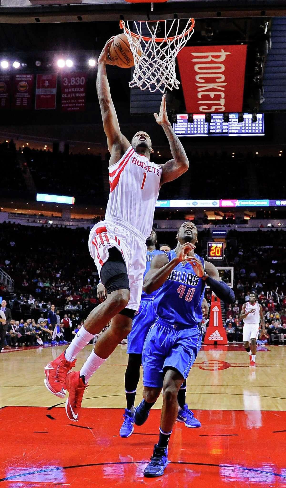 Houston Rockets forward Trevor Ariza (1) shoots past Dallas Mavericks forward Harrison Barnes (40) during the first half of an NBA basketball game, Saturday, Dec. 10, 2016, in Houston. (AP Photo/Eric Christian Smith)