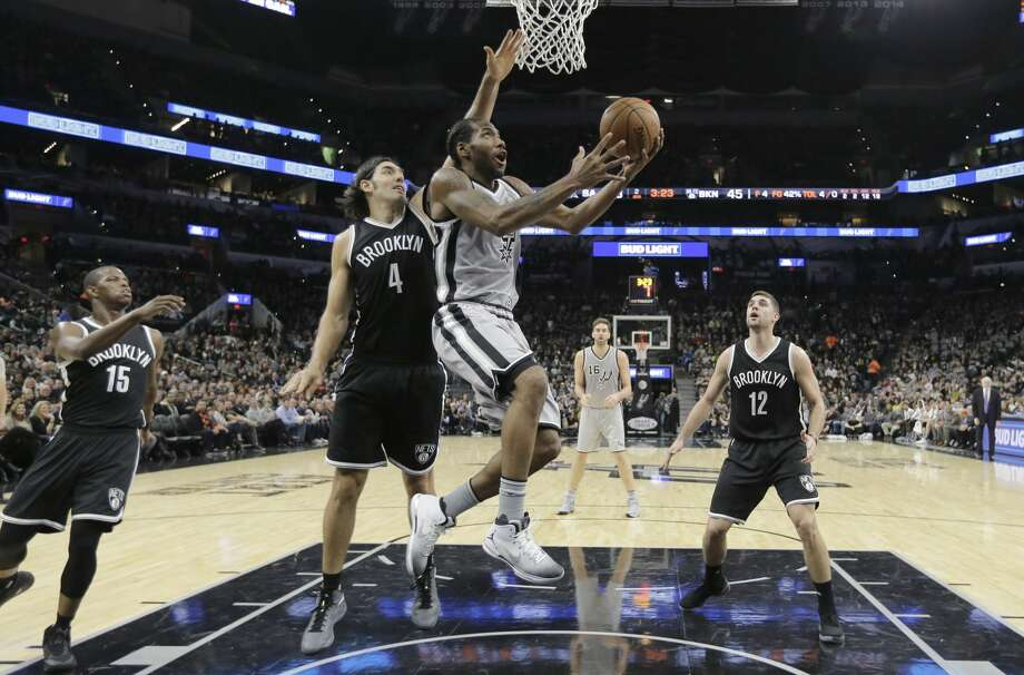 San Antonio Spurs forward Kawhi Leonard (2) drives around Brooklyn Nets forward Luis Scola (4) to score during the first half of an NBA basketball game, Saturday, Dec. 10, 2016, in San Antonio. (AP Photo/Eric Gay) Photo: Eric Gay/Associated Press