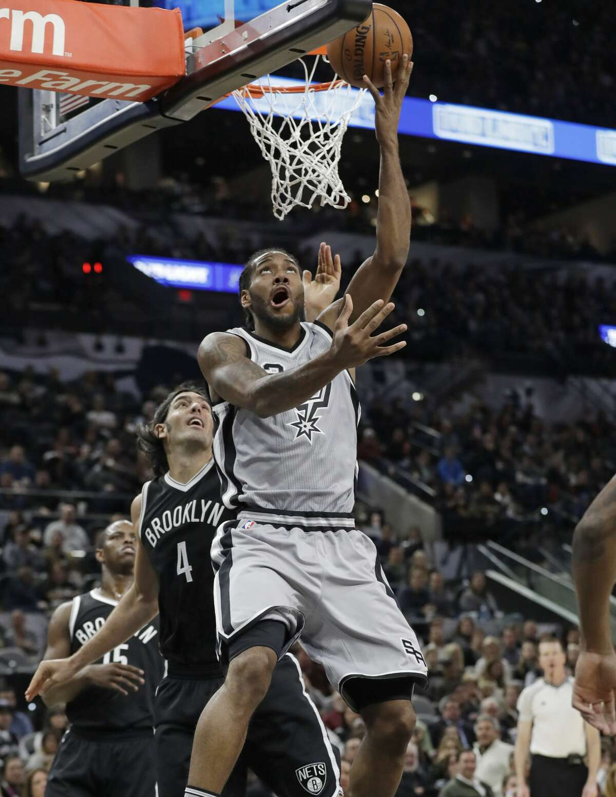 San Antonio Spurs forward Kawhi Leonard (2) drives around Brooklyn Nets forward Luis Scola (4) to score during the first half of an NBA basketball game, Saturday, Dec. 10, 2016, in San Antonio. (AP Photo/Eric Gay)
