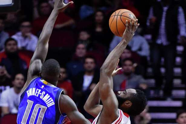 Houston Rockets guard James Harden, right, shoots as Dallas Mavericks forward Dorian Finney-Smith (10) defends during the first half of an NBA basketball game, Saturday, Dec. 10, 2016, in Houston.