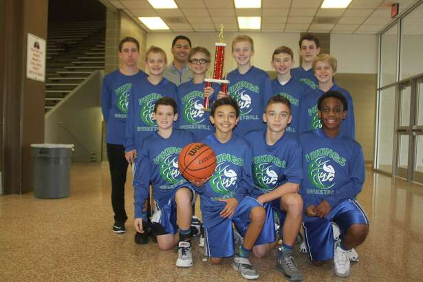 The Fairmont Junior High 7B boys basketball team celebrate their newly-won San Jacinto Invitational championship by posing with their trophy after the 41-31 win Saturday afternoon. It capped a picture-perfect 4-0 record.