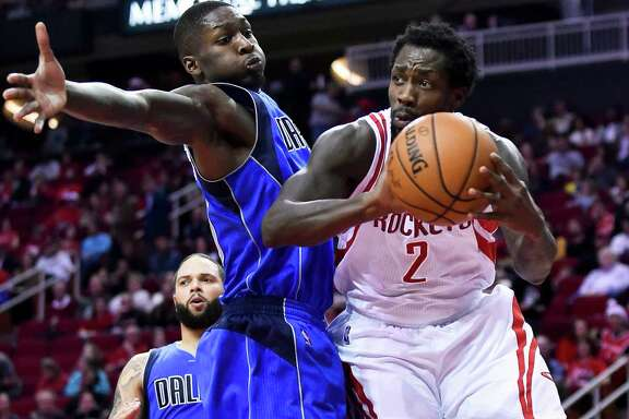 Rockets guard Pat Beverley, right, looks to pass as Mavericks forward Dorian Finney-Smith defends during the second half Saturday night. Beverley saw his way clear for 15 points in the victory at Toyota Center.