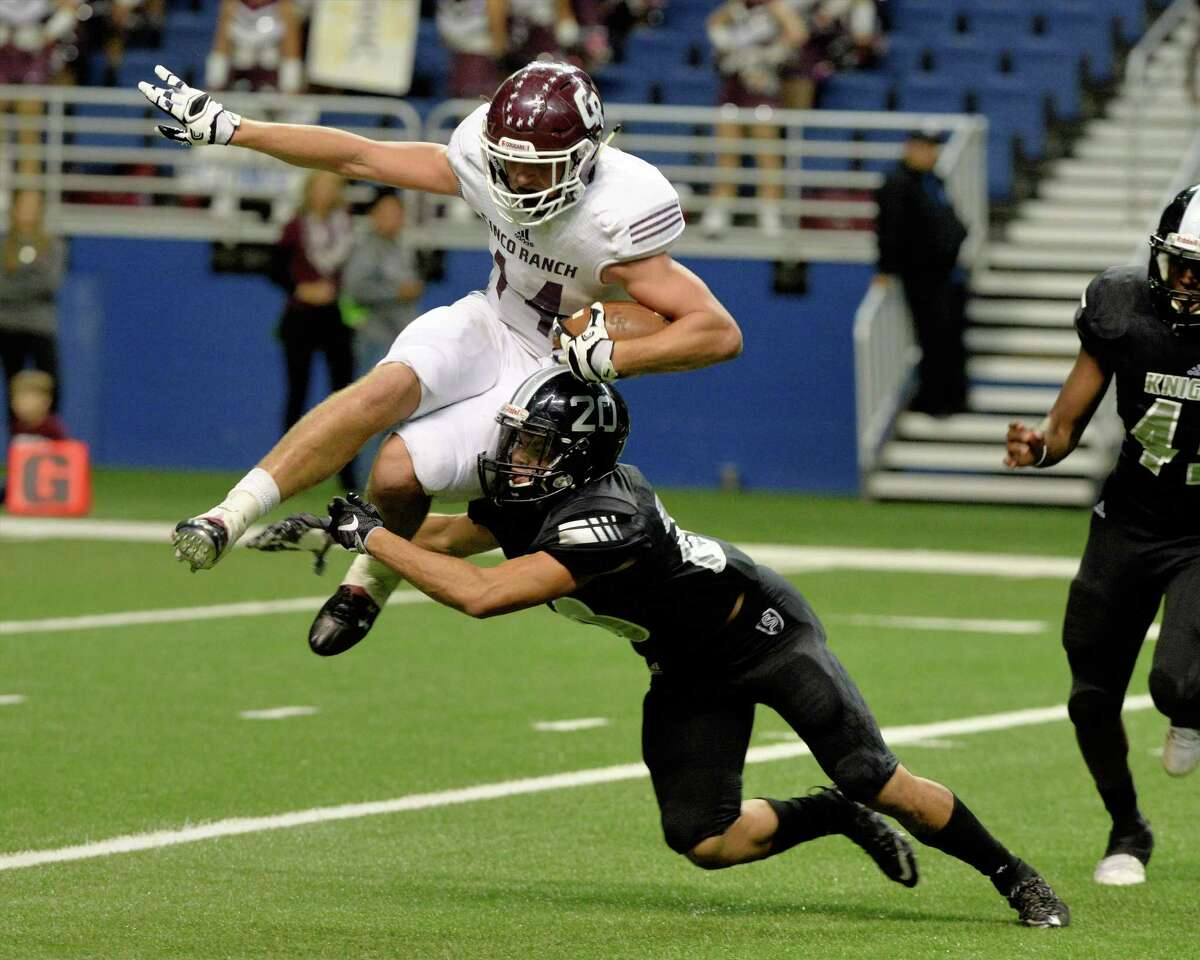 Brant Kuithe (14) of Cinco Ranch is tackled by Alex Allamby (20) of Cibolo Steele during the second half of the Conference 6A Division II State Semi-Final playoff game between the Cinco Ranch Cougars and the Cibolo Steele Knights on Saturday December 10, 2016 at the Alamodome, San Antonio, TX.