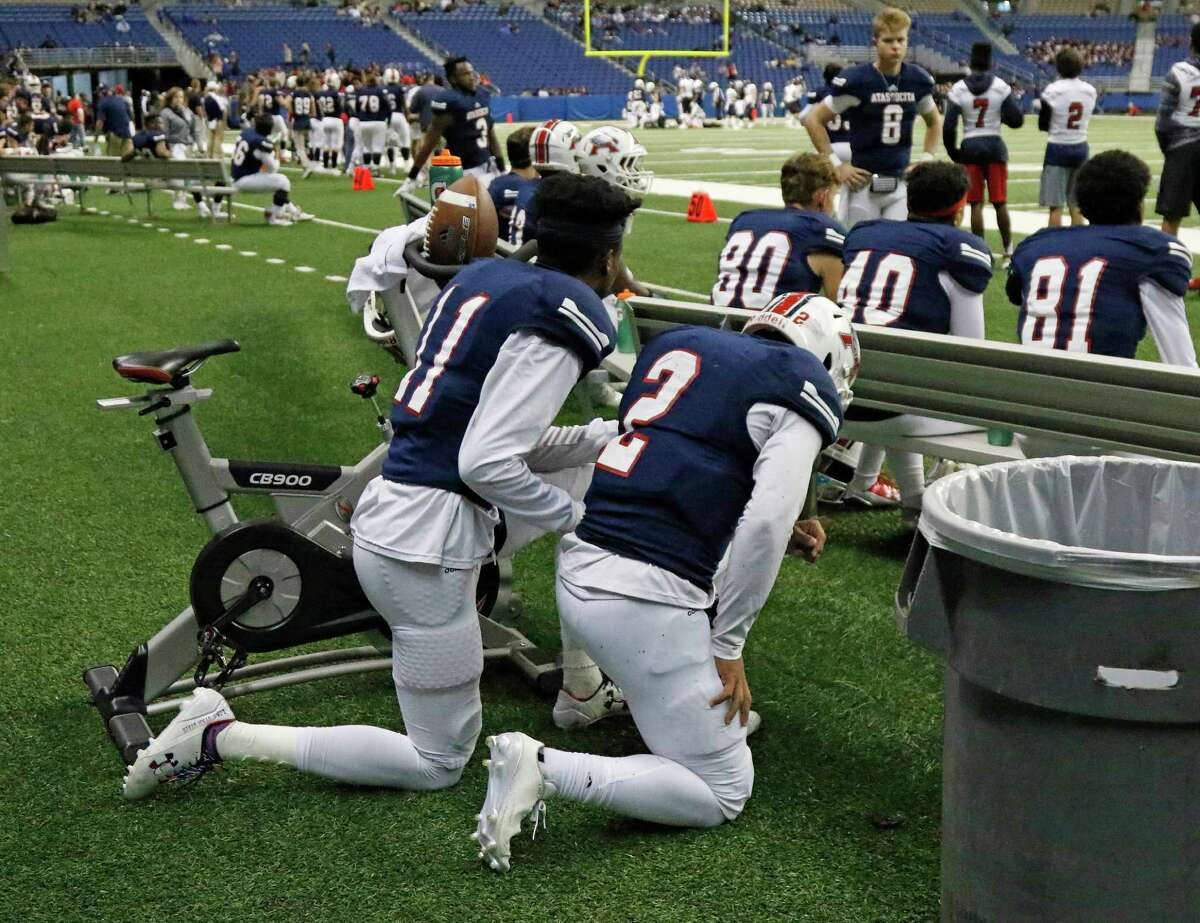 Atascocita Lujuan Winningham,11, and qb Daveon Boyd kneel behind the bench when they fell far behind from Lake Travis from the Class 6A Division I state semifinal high school football game between Lake Travis and Atascocita at the Alamodome on Saturday , December 10, 2016.