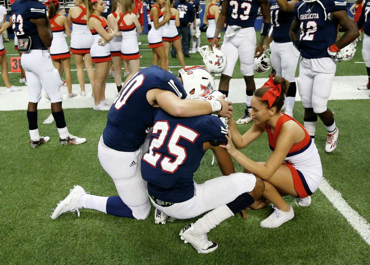 Atascocita Darien Taylor is consoled by player and cheerleader at end of the game from the Class 6A Division I state semifinal high school football game between Lake Travis and Atascocita at the Alamodome on Saturday , December 10, 2016.