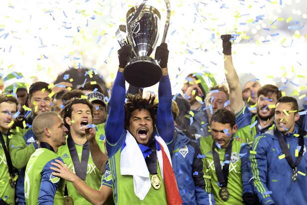 Seattle Sounders Roman Torres, center, hoists the trophy  after winning the MLS Cup soccer final over Toronto FC in Toronto, Saturday, Dec. 10, 2016. Frank Gunn/The Canadian Press via AP)