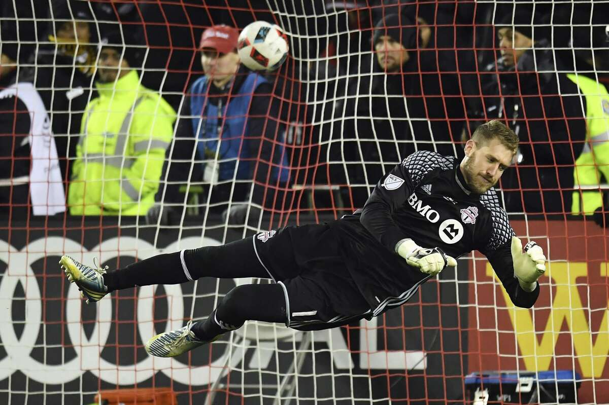 Toronto FC goalkeeper Clint Irwin (1) dives but fails to make a save as the winning goal goes in the net from Seattle Sounders defender Roman Torres during penalty kicks in the MLS Cup soccer final in Toronto, Saturday, Dec. 10, 2016.