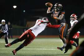 McClymonds Warriors quarterback Emoreea Fountain (1) is hit as he throws against East Nicolaus Spartans linebacker Ian Novak (77) during the first half of a football game on Saturday, Dec. 10, 2016 in Hayward, Calif. The football game was the CIF regional NorCal 5-A. The Warriors lead 20-14 at half.