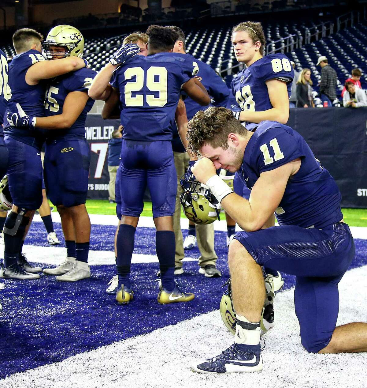 Klein Collins wide receiver Zach Skrehot (11) takes a knee while teammates hug and cry after losing to DeSoto in the Class 6A, Division II state semifinals, at NRG Stadium, Saturday, Dec. 10, 2016, in Houston.