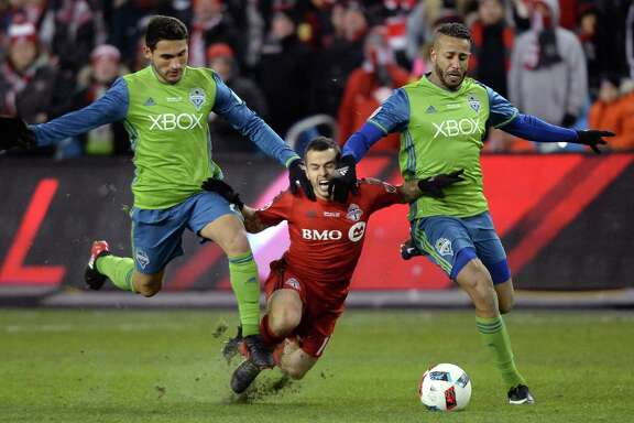 Toronto FC forward Sebastian Giovinco, center, is feeling the squeeze after being sandwiched by the Sounders' Cristian Roldan, left, and Tyrone Mears.