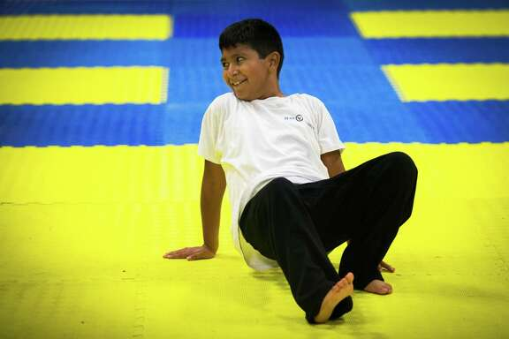 Carlos Gonzalez, 8, warms up during taekwondo class, Tuesday, Nov. 1, 2016, in Houston. Gonzalez's mother enrolled him taekwondo to help him channel his energy toward productive activities. His teachers kept telling his mother that his attitude was of a spoiled child. Now the doctors say that his defiance is part of autism, not a behavioral problem.