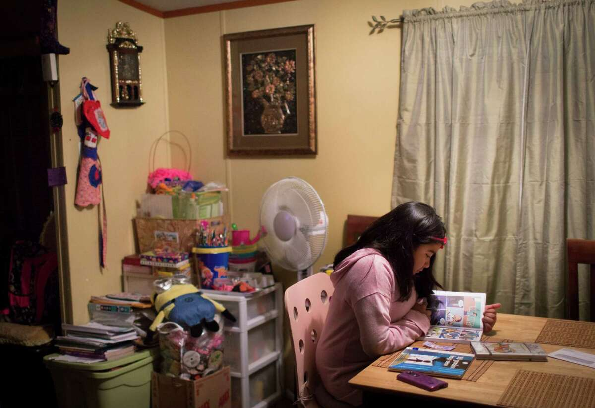 Ashley Rodriguez, 9, tries to read a graphic novel, Monday, Dec. 5, 2016, in Pflugerville. Rodriguez is a fifth grader who just recently got placed in special education after years of fighting by her parents. Cardenas says her daughter has delayed reactions and struggles to read and understand what she is reading.