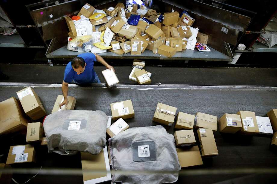 A UPS worker sorts packages at the UPS Sweetwater hub. The post-holiday period has always brought a spike in returns, but surging online sales and perks such as free shipping have complicated the process for retailers. Photo: Michael Ciaglo /Houston Chronicle / © 2016  Houston Chronicle