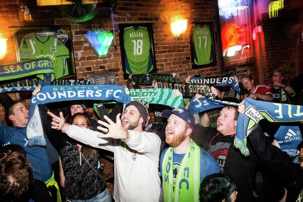 Seattle Sounders fans celebrate following their win over Toronto FC in the MLS Cup, at Fuel Sports in Pioneer Square on Saturday, Dec. 10, 2016.