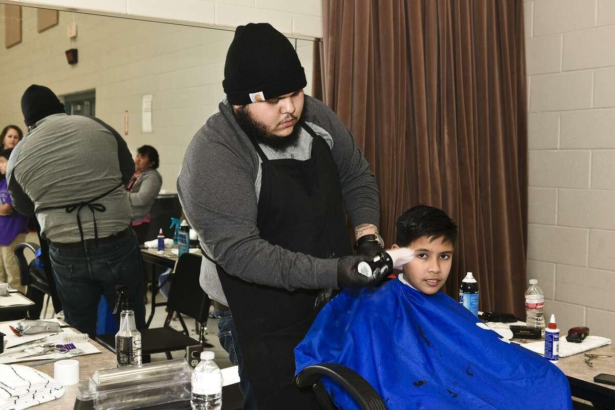 El voluntario Jaime García corta el cabello de Andrés Otero el sábado por la tarde en el Complejo de Actividades Estudiantiles durante un evento navideño para estudiantes migrantes.