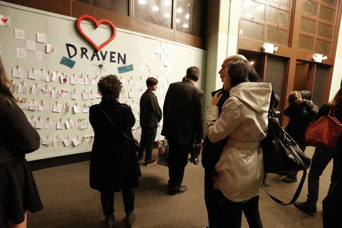 A crowd gathers around a display with handwritten notes after the memorial for Draven McGill, who was killed in the Oakland fire, on Saturday Dec. 10, 2016 in San Francisco. Orchestral performance at Ruth Asawa School of the Arts to honor 17-year-old Draven McGill, a junior at the school who was one of the Oakland fire victims and is the son of a sheriff for the Alameda County Sheriff's Office.