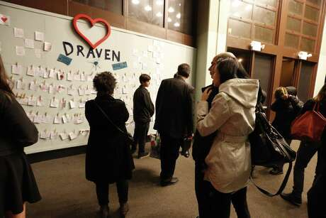 Crowd gather around a display with handwritten notes after the memorial for Draven McGill at Ruth Asawa School of the Arts in San Francisco.