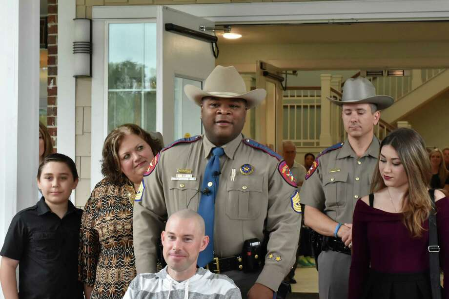 Blackburn receives an assist from fellow DPS trooper Sgt. Stephen Woodard as he leaves the hospital. He is surrounded by his family. He has a long road to recovery, but is grateful to be alive after surviving a horrific accident. Photo: David Taylor