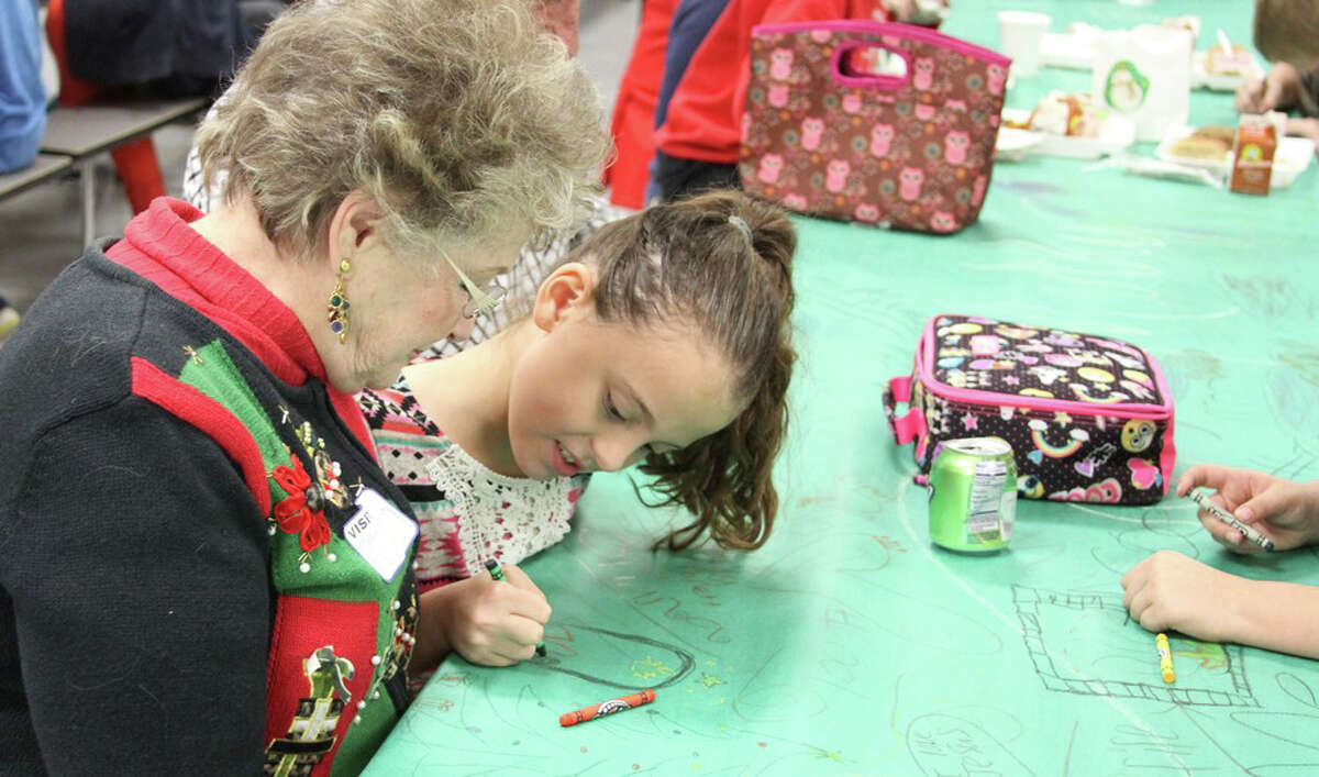 CIS student Briana Syphrett colored with her great-grandmother Vada Syphrett at the Christmas Luncheon on Thursday, Dec. 8.