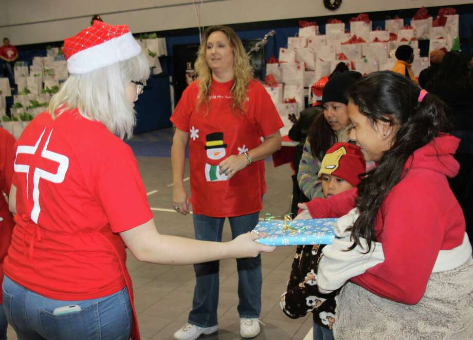 Elizabeth O'Dell (left) gives a gift to a child for the Angel Select Toy Drive. Photo: Jacob McAdams