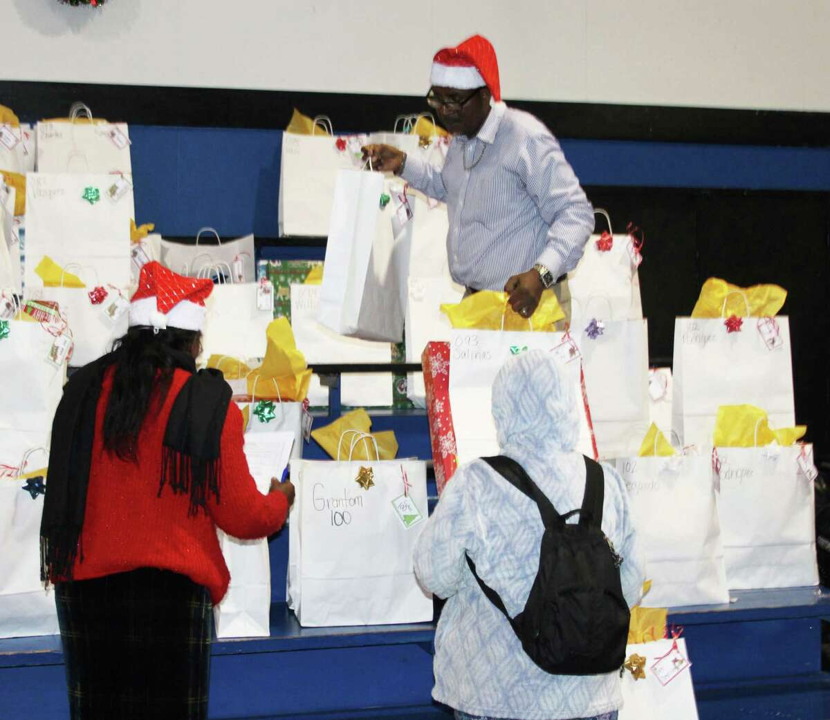 James Harrell (back) brings down a couple of bags containing pre-registered gifts for the Angel Select Toy Drive.