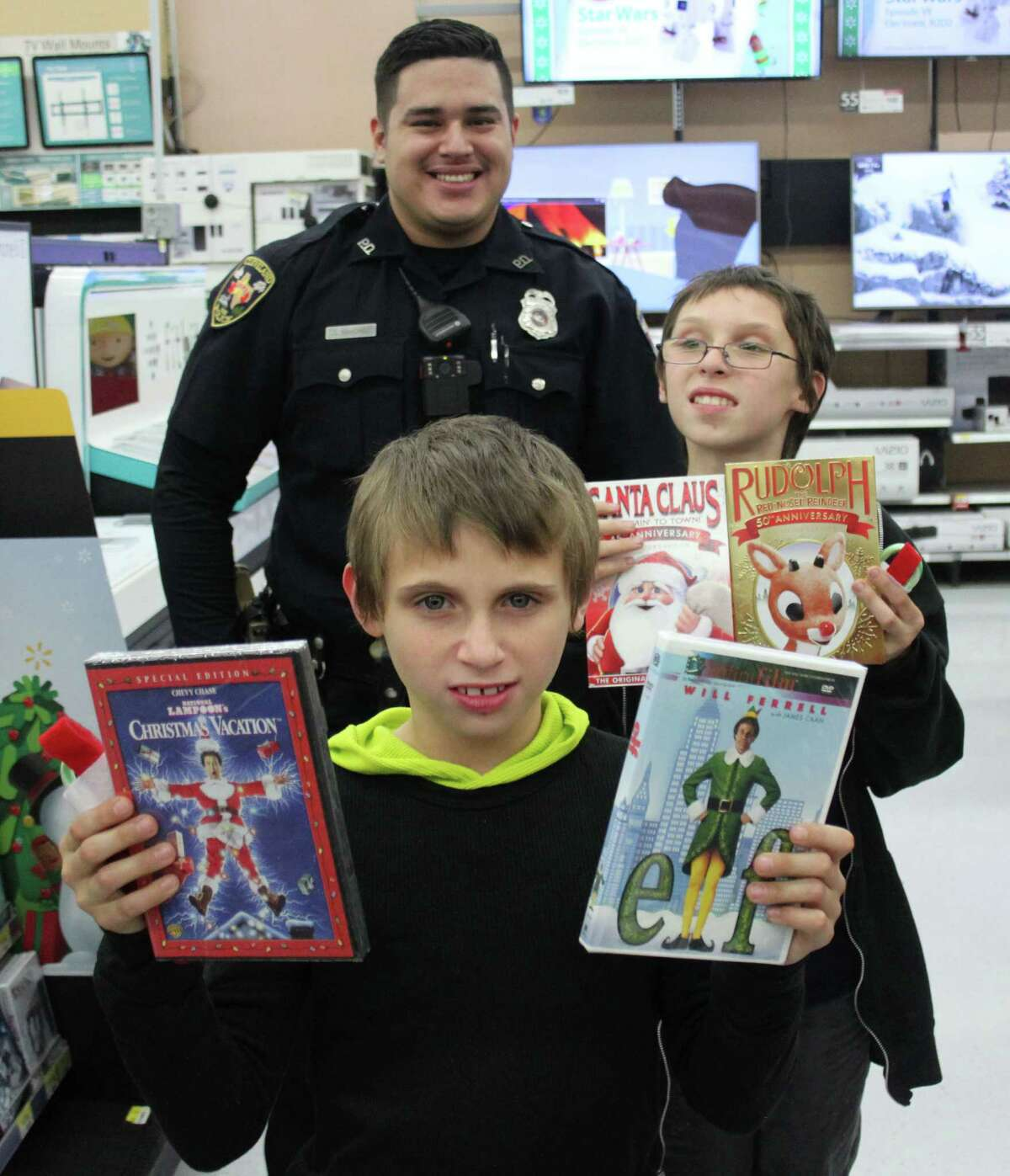 Zachariah DeCuir (front) and his brother John DeCuir (right) show off Christmas movies they plan to purchase their gift cards. Cleveland Police Department Patrol Officer Oscar Sanchez (back) assisted the two children in picking out movies.