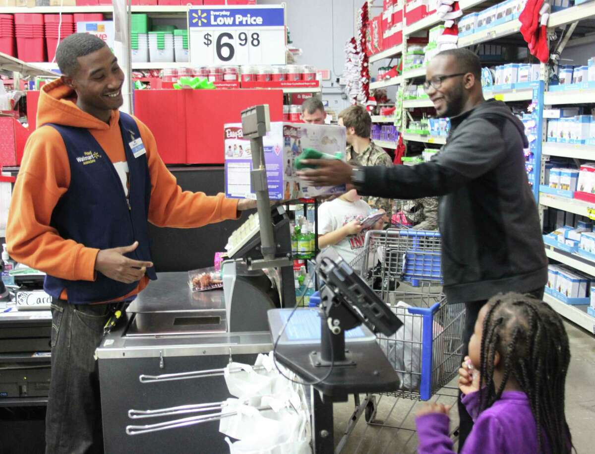 Walmart employee Jalen Carter (left) hands a newly purchased gift to Pastor Carrington to give to a young child.