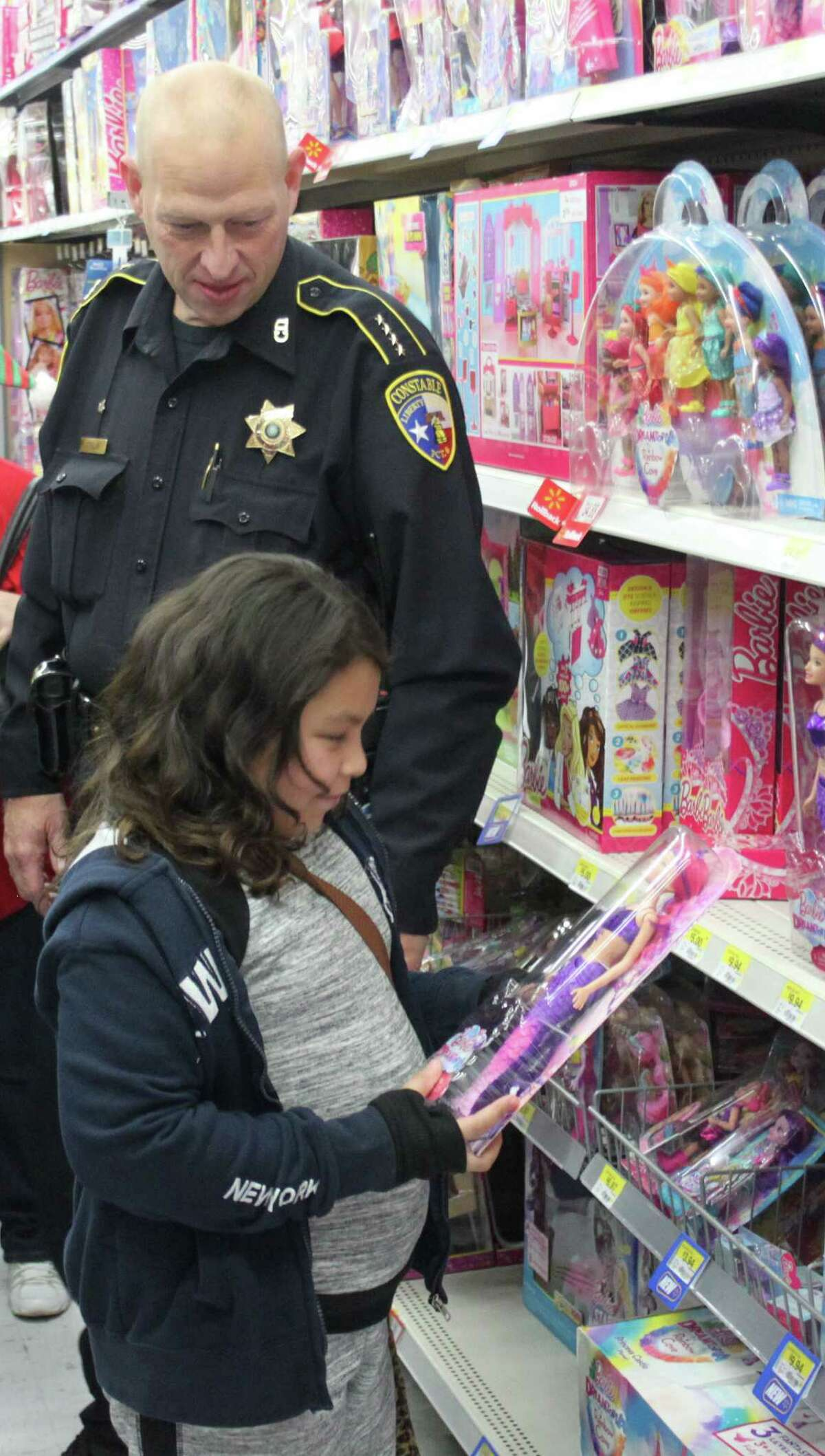 Liberty County Pct. 6 Constable John Joslin helps Juanita Moreno (front) pick out a new Barbie doll as part of the Shop with a Cop event at Cleveland Walmart.