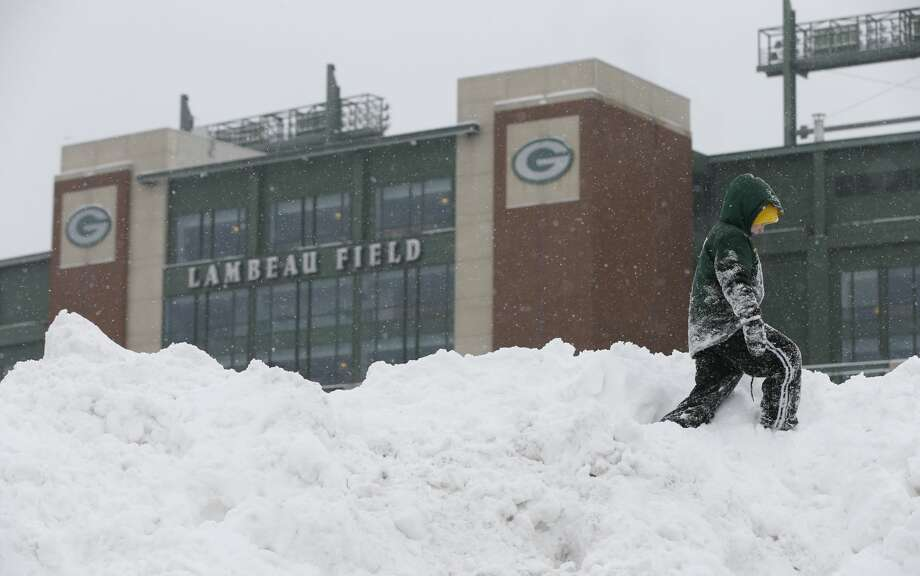 Nicholas Nesvacil walks on a pile of snow outside Lambeau Field before an NFL football game between the Green Bay Packers and the Seattle Seahawks Sunday, Dec. 11, 2016, in Green Bay, Wis. (AP Photo/Mike Roemer) Photo: Mike Roemer/AP