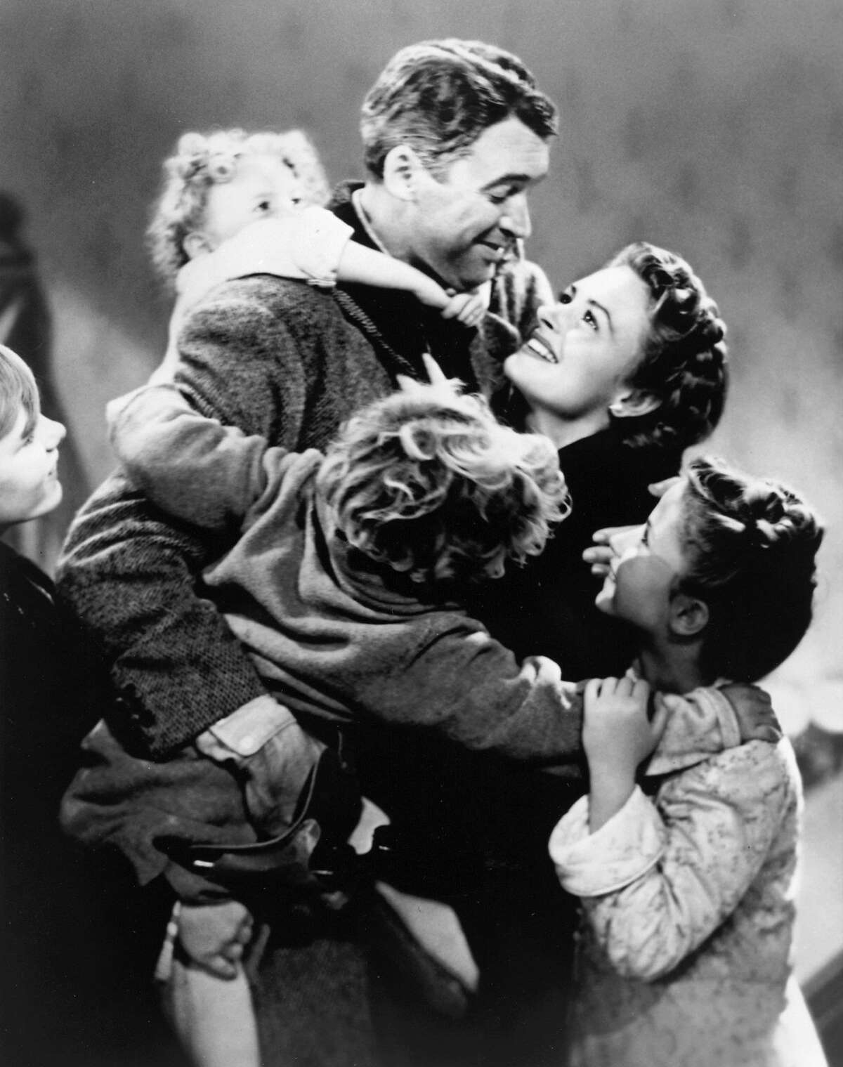 This image released by NBC shows James Stewart, center, and Donna Reed, background in a scene from Frank Capra's 1946 holiday classic,