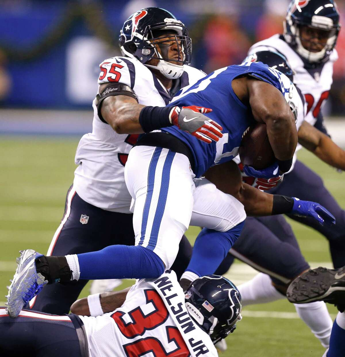 Houston Texans inside linebacker Benardrick McKinney (55) and defensive back Robert Nelson (32) tackle Indianapolis Colts running back Robert Turbin (33) during the second quarter of an NFL football game at Lucas Oil Stadium on Sunday, Dec. 11, 2016, in Indianapolis.