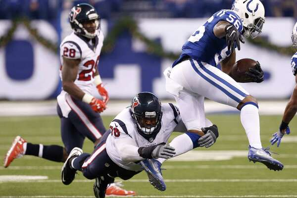 Indianapolis Colts linebacker Akeem Ayers (56) leaps to avoid Houston Texans tackle Duane Brown (76) after intercepting a pass by Brock Osweiler during the second quarter of an NFL football game at Lucas Oil Stadium on Sunday, Dec. 11, 2016, in Indianapolis.