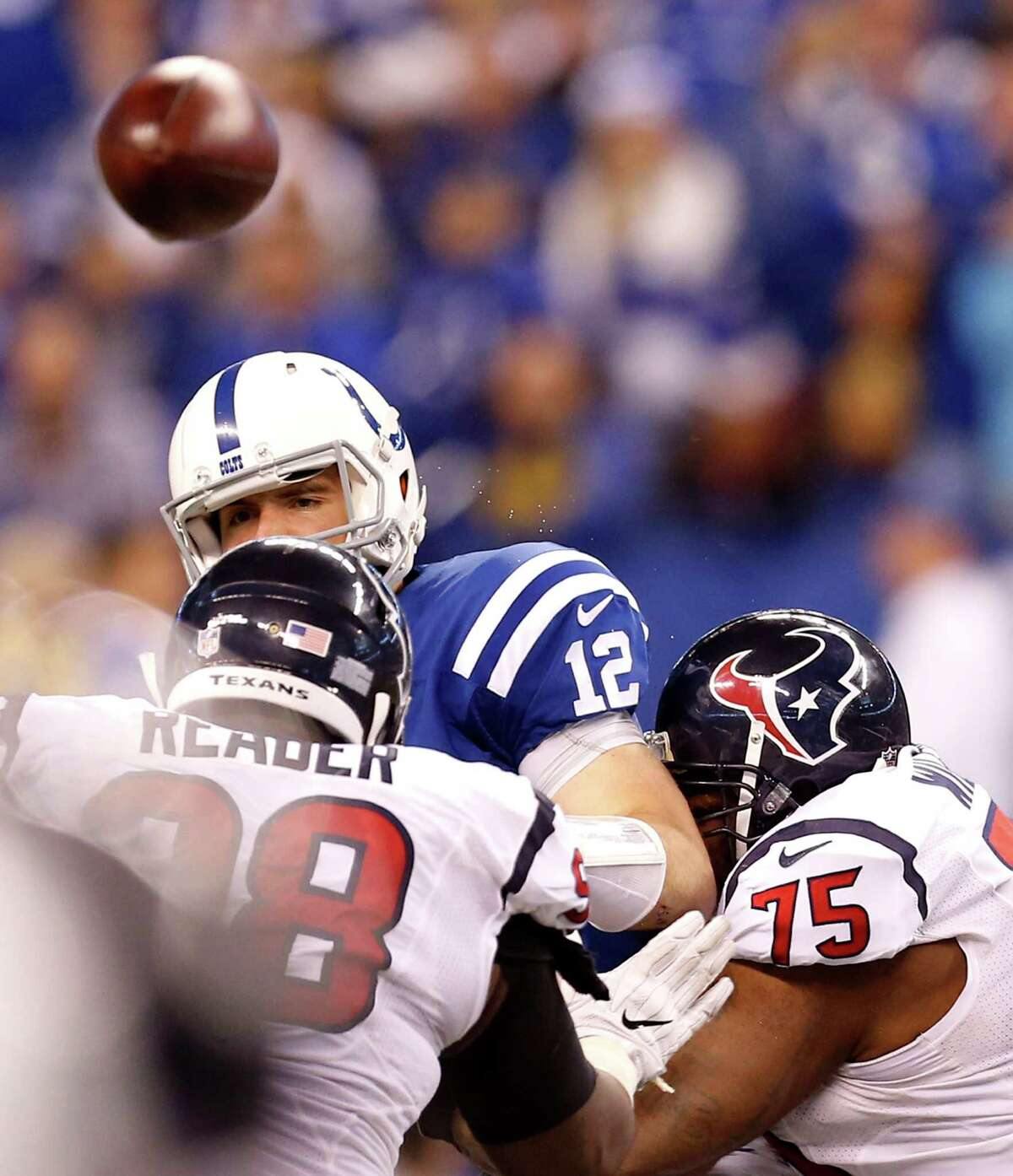 Indianapolis Colts quarterback Andrew Luck (12) throws an errant pass as he is hit by Houston Texans defensive end D.J. Reader (98) and nose tackle Vince Wilfork (75) during the fourth quarter of an NFL football game at Lucas Oil Stadium on Sunday, Dec. 11, 2016, in Indianapolis.