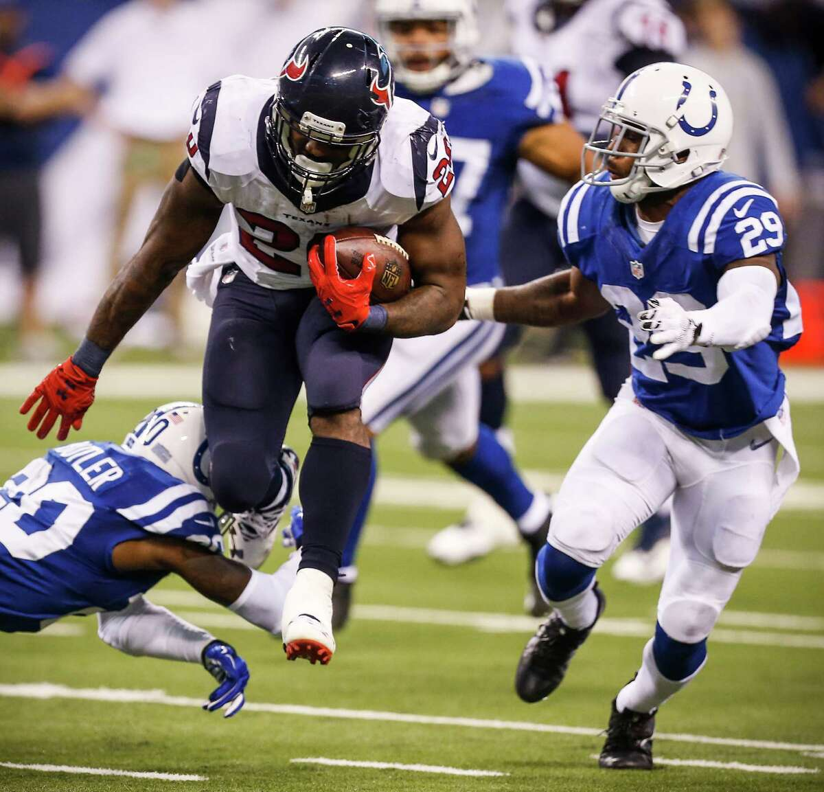 Houston Texans running back Lamar Miller (26) leaps past Indianapolis Colts cornerback Darius Butler (20) and strong safety Mike Adams (29) during the fourth quarter of an NFL football game at Lucas Oil Stadium on Sunday, Dec. 11, 2016, in Indianapolis.