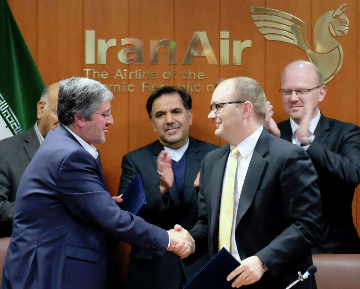 Farhad Parvaresh, left, chairman of Iran Air, and Fletcher Barkdull, Boeing regional director, finalize a contract Sunday in Tehran in the first deal of its kind since the 1979 Islamic revolution.