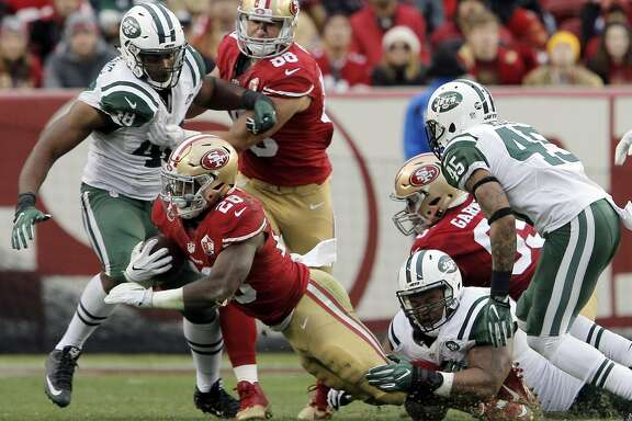 Carlos Hyde (28) is wrapped up by Deon Simon (93) in the second half as the San Francisco 49ers played the New York Jets at Levi's Stadium in Santa Clara, Calif., on Sunday, December 11, 2016. The Jets won in 23-17 overtime.