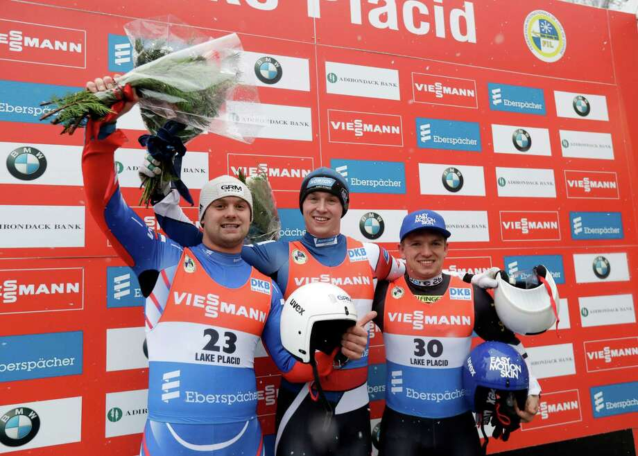 Tucker West, center, of the United States, celebrates after winning the men's luge World Cup race with Semen Pavlichenko, left, of Russia, second place, and Wolfgang Kindl, of Austria, third place, on Friday, Dec. 2, 2016, in Lake Placid, N.Y. (AP Photo/Mike Groll) ORG XMIT: NYMG127 Photo: Mike Groll / Copyright 2016 The Associated Press. All rights reserved.