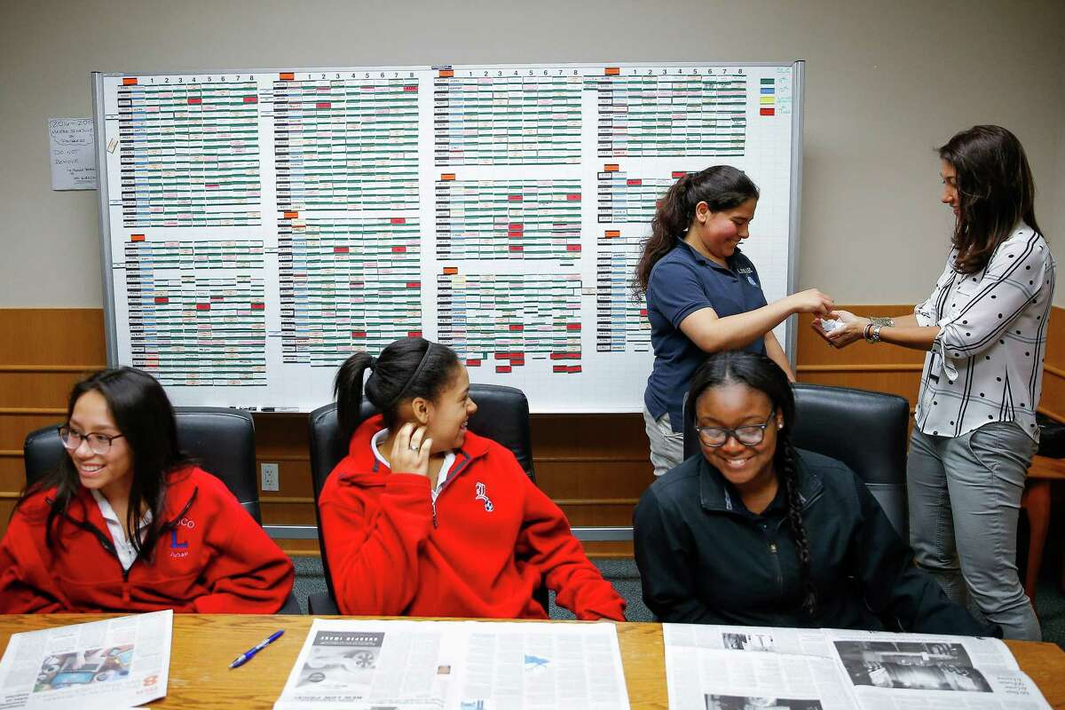 Lamar High School senior Reem Abuabeeleh picks an article to discuss from Laskin during a meeting of Women on the Way Up.