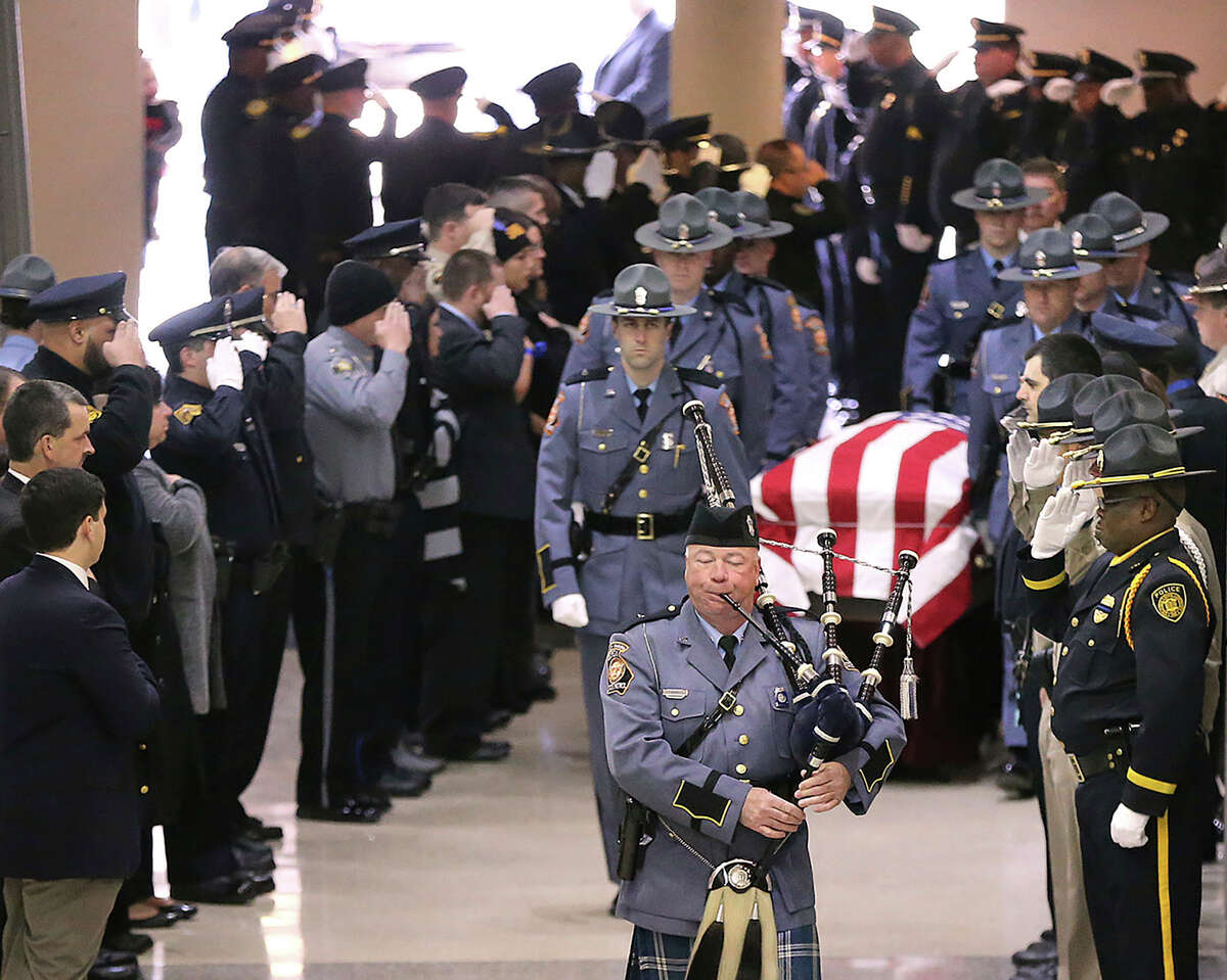 Americus police officers salute the casket of fallen police officer Nicholas Ryan Smarr at his funeral service at the Georgia Southwestern State University Storm Dome on Sunday, Dec. 11, 2016, in Americus, Ga. Smarr and his lifelong friend, Georgia Southwestern State University campus police officer Jody Smith, were killed responding to a domestic violence call on Wednesday. (Curtis Compton/Atlanta Journal-Constitution via AP)
