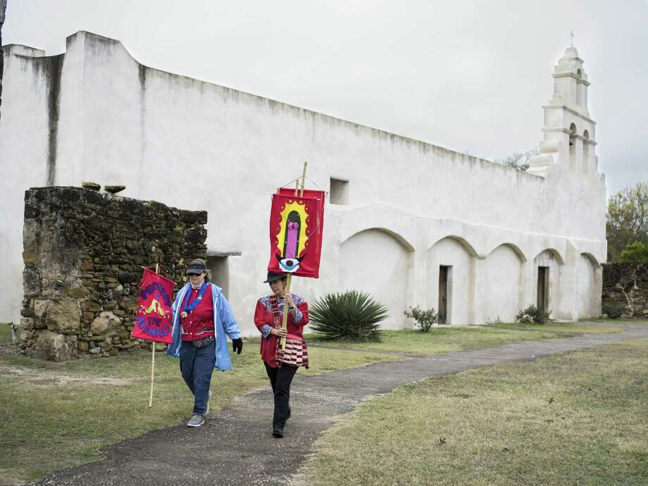 Terry Yba–ez, right, and Margaret Murphy, left, both on the Mission San Jose Neighborhood Association pass in front of San Juan during a mission pilgrimage that started from Mission Concepci—n and made stops at missions San Jose, San Juan and finished at Mission Espada on Sunday, December 11, 2016. The walk is meant to honor the feast day of La Virgen de Guadalupe (Our Lady of Guadalupe) and to bring awareness to the protection of the missions from what the organizers call more commercial interests, like planned developments in close proximity to the missions. Photo: Photos By Matthew Busch / For The San Antonio Express-News / © Matthew Busch