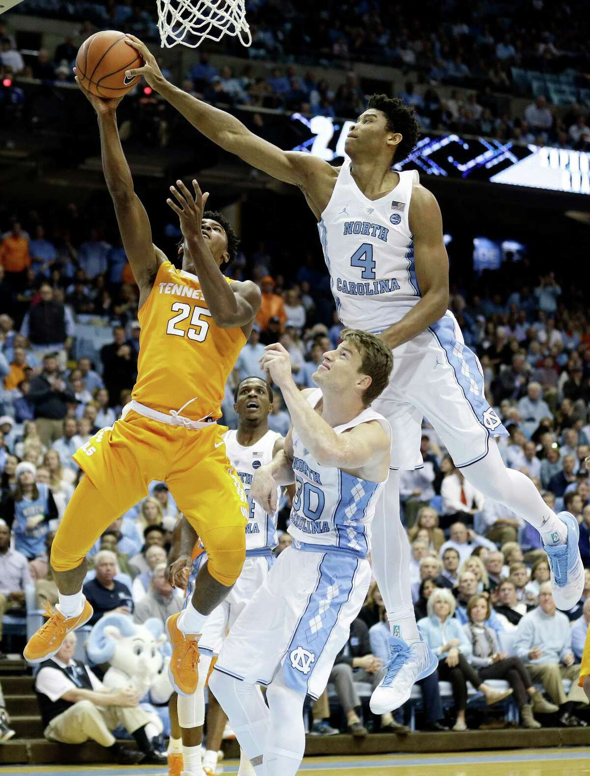 North Carolina's Isaiah Hicks (4) goes over the back of teammate Stilman White to block a shot by Tennessee's Shembari Phillips (25) in the second half.