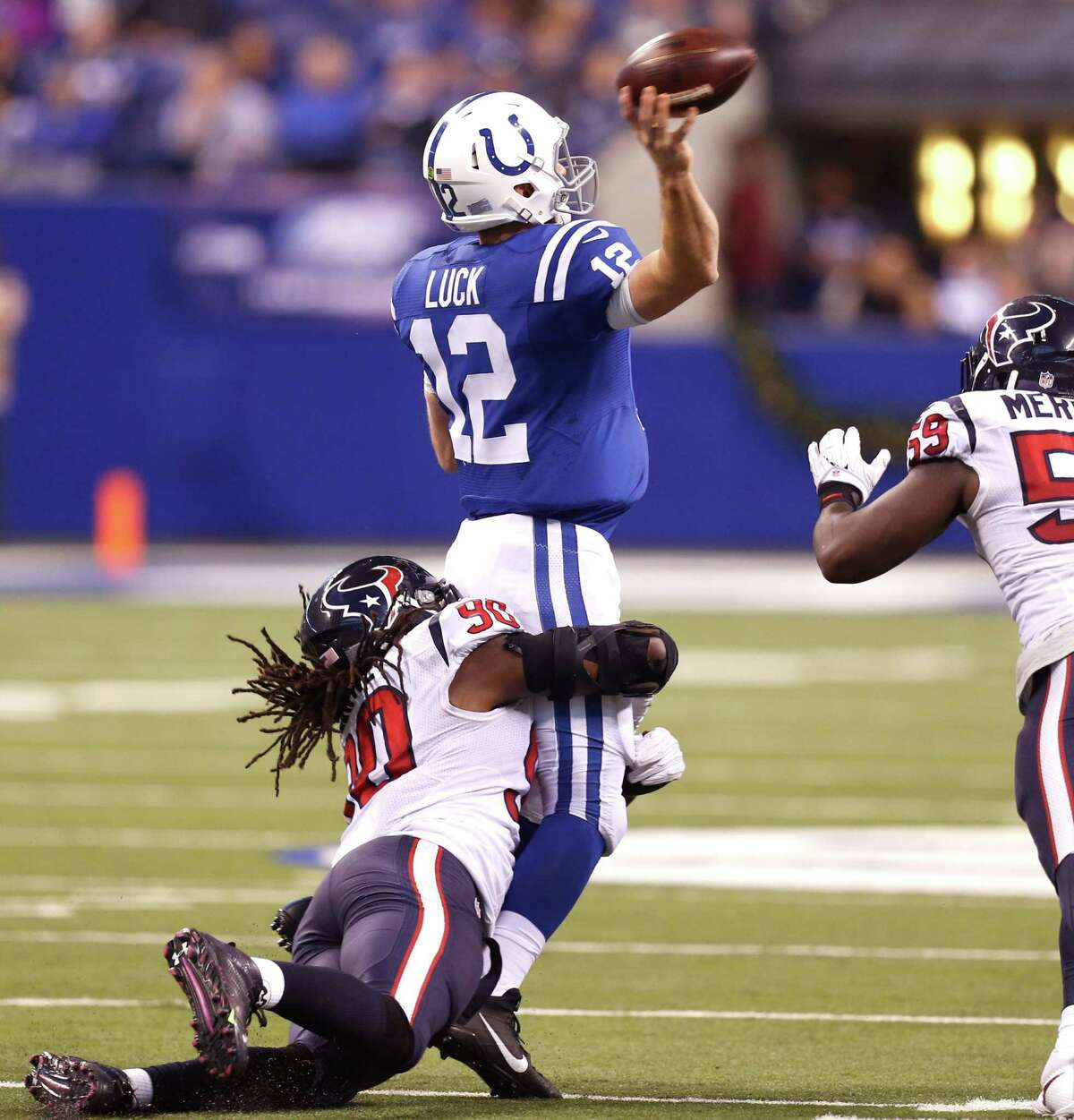 Texans defensive end Jadeveon Clowney (90) wraps up Colts quarterback Andrew Luck, whose pass would be intercepted by free safety Andre Hal at the Indianapolis 42 and returned to the 18, setting up a Nick Novak field goal early in the third quarter.