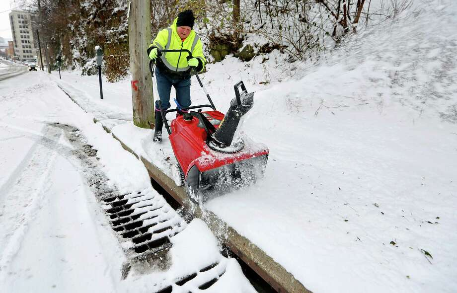 City of Dubuque employee Charlie Leirmoe-Kaiser clears snow from the sidewalk along Eighth Street in Dubuque, Iowa, on Sunday, Dec. 11, 2016. Dubuque received 4 inches of snow overnight, less than forecasters had expected. (Nicki Kohl/Telegraph Herald via AP) ORG XMIT: IADUB705 Photo: Nicki Kohl / Telegraph Herald