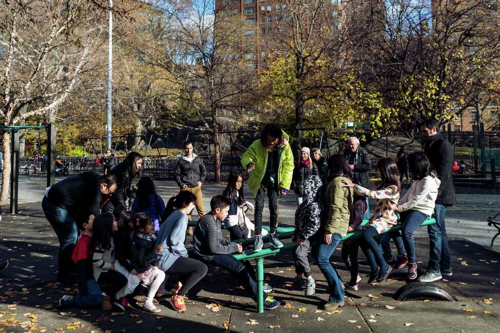 Children play on a seesaw in the Classic Playground in Riverside Park in New York, Nov. 27, 2016. Officials say it is the last playground to have old-style seesaws in New York CityOs public playgrounds. (An Rong Xu/The New York Times) ORG XMIT: XNYT8