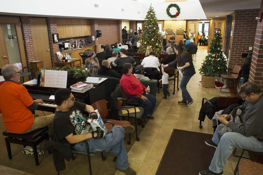 Participants wait their turn in a lobby while volunteer David Moll, of Midland, plays Christmas songs on a piano during a free dental clinic sponsored by Midland Seventh-day Adventist Church at the Midland Community Center on Sunday. Photo: Theophil Syslo