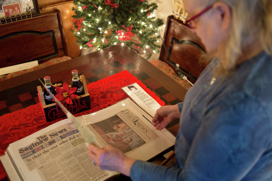 FILE — Deanna McRoberts of Midland flips through a memorial album about her son, Greg McRoberts, who was killed when a car struck him while he was riding a bicycle on South Meridian Road. Investigators haven't discovered who hit McRoberts. The book is filled with family photos and newspaper clippings about Greg. 'Around this time of year I like to look through the album,' McRoberts said. 'To reminiscence. It's nice.' (BRITTNEY LOHMILLER | Midland Daily News) / Midland Daily News