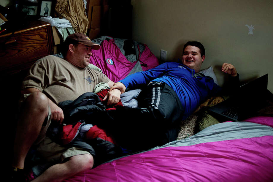 Dennis Mashue, left, smiles at his son Tucker Mashue as the pair lounges on sleeping bags on April 22 at their Midland home.